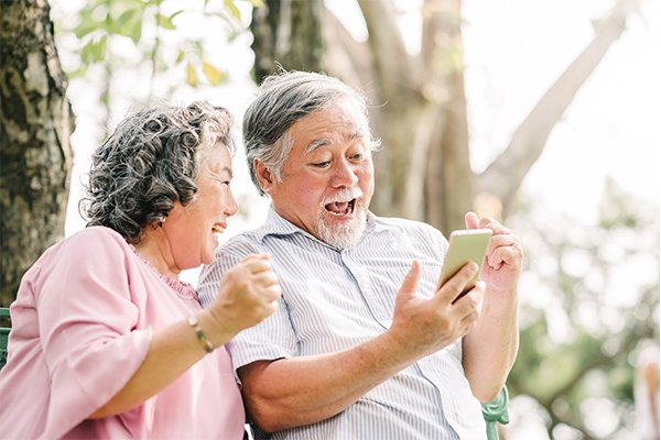 ymt blog how to save on your phone bill when traveling older couple laughing on smartphone