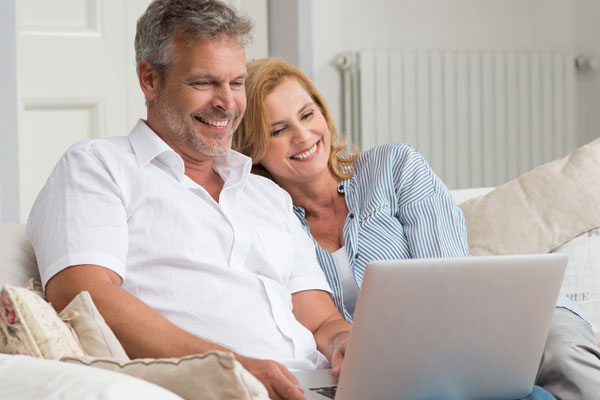 ymt-blog-how-to-set-up-a-travel-budget-for-your-first-trip-abroad-older-couple-happy-on-the-computer