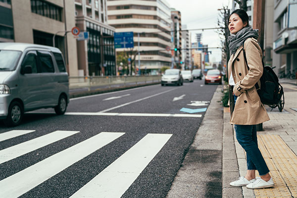 ymt-blog-japanese-customs-dos-and-donts-for-visiting-japan-woman-waiting-at-crosswalk