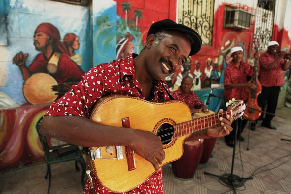 Street musician in Cuba playing guitar with art mural in the background
