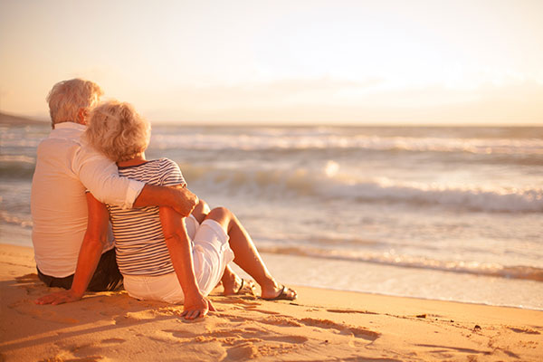 Couple-Relaxing-on-Beach_IS-ymt-blog-benefits-of-taking-more-vacations-couple-relaxing-on-beach