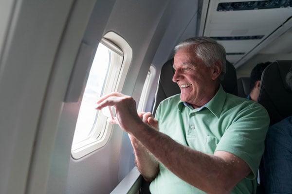 senior-man-on-plane-window-seat-taking-pictures-iS-1028463276 (1)