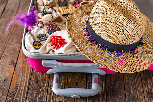 ymt-blog-how-to-pack-gifts-and-souvenirs-from-your-trip-woman-packing-suitcase-filled-with-keepsakes