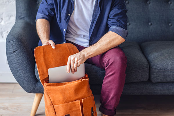 ymt-blog-tips-for-staying-cyber-safe-while-traveling-man-packing-laptop